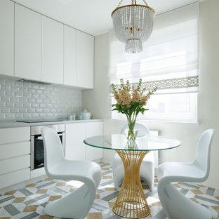 Стильный дизайн: линейная кухня в современном стиле с обеденным столом, плоскими фасадами, белыми фасадами, белым фартуком, фартуком из плитки кабанчик, техникой из нержавеющей стали, разноцветным полом и серой столешницей - последний тренд