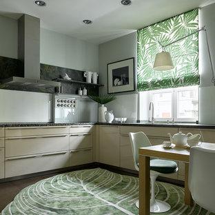 На фото: угловая кухня в современном стиле с плоскими фасадами, бежевыми фасадами, белым фартуком, коричневым полом и черной столешницей с