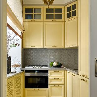 На фото: маленькая отдельная, угловая кухня в стиле неоклассика (современная классика) с врезной раковиной, фасадами с утопленной филенкой, желтыми фасадами, серым фартуком, техникой под мебельный фасад, серым полом и серой столешницей без острова