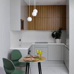 Неиссякаемый источник вдохновения для домашнего уюта: маленькая п-образная кухня-гостиная в современном стиле с врезной раковиной, плоскими фасадами, серыми фасадами, белым фартуком, белым полом и белой столешницей