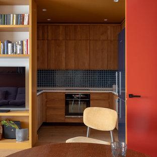 На фото: кухни в современном стиле с плоскими фасадами, фасадами цвета дерева среднего тона, синим фартуком и белой столешницей