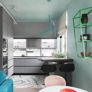 На фото: угловые кухни-гостиные в современном стиле с плоскими фасадами, серыми фасадами и техникой из нержавеющей стали без острова