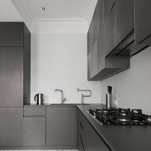 На фото: угловые кухни среднего размера в современном стиле с обеденным столом, врезной раковиной, плоскими фасадами, черными фасадами, фартуком из стекла, мраморным полом и белым фартуком без острова