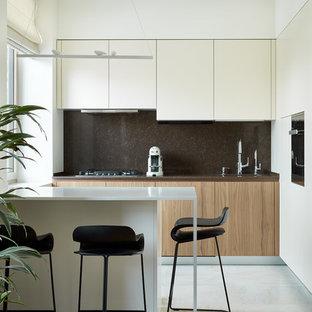 На фото: угловая кухня-гостиная в современном стиле с плоскими фасадами, светлыми деревянными фасадами, коричневым фартуком, островом, белым полом и коричневой столешницей с