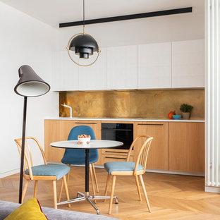 Пример оригинального дизайна интерьера: маленькая линейная кухня в современном стиле с обеденным столом, врезной раковиной, плоскими фасадами, столешницей из кварцита, бежевым фартуком, черной техникой, белой столешницей, паркетным полом среднего тона, светлыми деревянными фасадами и коричневым полом