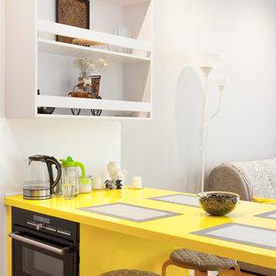 Идея дизайна: кухня в современном стиле с обеденным столом, черной техникой, паркетным полом среднего тона, полуостровом, желтой столешницей, желтыми фасадами, плоскими фасадами и коричневым полом