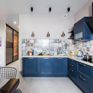 Стильный дизайн: угловая кухня в стиле современная классика с обеденным столом, фасадами с утопленной филенкой, синими фасадами, разноцветным фартуком, фартуком из цементной плитки, техникой под мебельный фасад, бежевым полом и белой столешницей - последний тренд