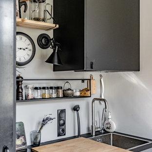 Свежая идея для дизайна: прямая кухня в стиле лофт с накладной раковиной, плоскими фасадами, серыми фасадами, белым фартуком и черной столешницей - отличное фото интерьера
