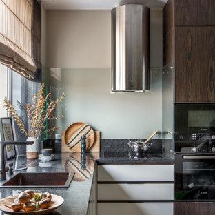 Стильный дизайн: угловая кухня среднего размера в современном стиле с накладной раковиной, плоскими фасадами, белыми фасадами, фартуком из стекла, черной техникой, бежевым полом и черной столешницей без острова - последний тренд