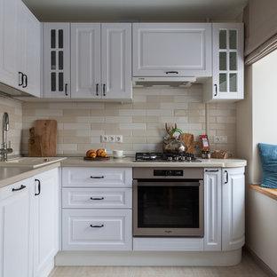 Неиссякаемый источник вдохновения для домашнего уюта: маленькая угловая, отдельная кухня в стиле современная классика с накладной раковиной, фасадами с выступающей филенкой, белыми фасадами, фартуком из керамической плитки, техникой из нержавеющей стали, полом из керамогранита, бежевым полом, бежевым фартуком и бежевой столешницей без острова