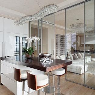 Ispirazione per una grande cucina contemporanea con ante lisce, ante bianche, elettrodomestici in acciaio inossidabile, parquet chiaro e isola