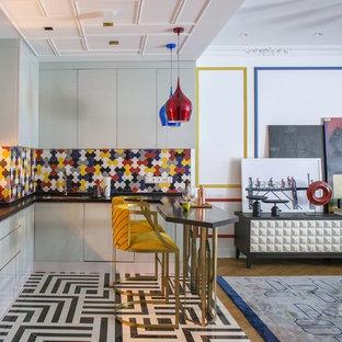 Пример оригинального дизайна: угловая кухня-гостиная среднего размера в стиле фьюжн с врезной раковиной, плоскими фасадами, белыми фасадами, разноцветным фартуком, разноцветным полом, черной столешницей и полуостровом