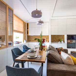 Источник вдохновения для домашнего уюта: прямая кухня-гостиная среднего размера в современном стиле с плоскими фасадами, белыми фасадами, коричневым фартуком, черной техникой, белым полом и белой столешницей