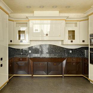 Пример оригинального дизайна интерьера: п-образная кухня-гостиная в стиле современная классика с накладной раковиной, темными деревянными фасадами, черным фартуком, черной техникой, коричневым полом и черной столешницей