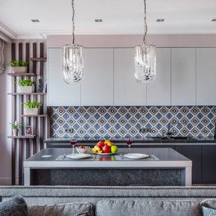 Свежая идея для дизайна: кухня-гостиная в современном стиле с накладной раковиной, плоскими фасадами, серыми фасадами, разноцветным фартуком, техникой из нержавеющей стали, островом и черной столешницей - отличное фото интерьера