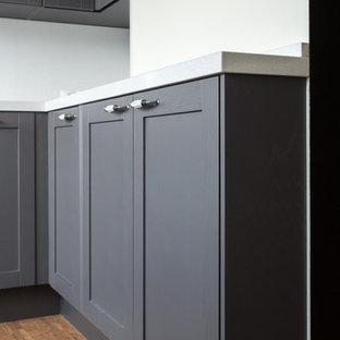 Minimalistisk inredning av ett avskilt, mellanstort vit vitt l-kök, med en nedsänkt diskho, skåp i shakerstil, grå skåp, bänkskiva i kvarts, vitt stänkskydd, stänkskydd i sten, svarta vitvaror, korkgolv och brunt golv