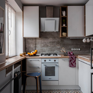 This is an example of a small contemporary l-shaped separate kitchen in Moscow with a drop-in sink, flat-panel cabinets, white cabinets, wood benchtops, grey splashback, white appliances, no island, multi-coloured floor and brown benchtop.