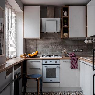 Источник вдохновения для домашнего уюта: маленькая угловая, отдельная кухня в современном стиле с накладной раковиной, плоскими фасадами, белыми фасадами, деревянной столешницей, серым фартуком, белой техникой, разноцветным полом и коричневой столешницей без острова