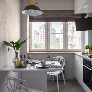 Стильный дизайн: маленькая угловая кухня в современном стиле с плоскими фасадами, белыми фасадами, черной техникой, серым полом, обеденным столом и бежевой столешницей без острова - последний тренд