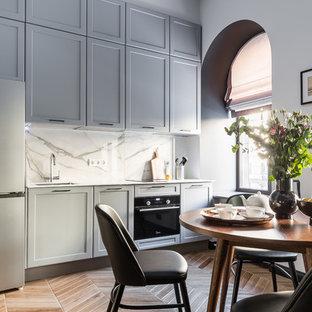 Создайте стильный интерьер: маленькая линейная кухня в стиле современная классика с обеденным столом, серыми фасадами, столешницей из акрилового камня, врезной раковиной, фасадами в стиле шейкер, белым фартуком, техникой из нержавеющей стали, полом из цементной плитки, коричневым полом и белой столешницей без острова - последний тренд
