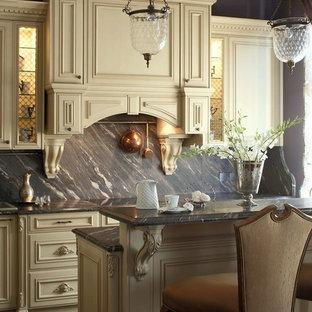 На фото: кухня в классическом стиле с бежевыми фасадами, разноцветным фартуком и фартуком из каменной плиты с