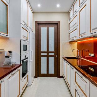 На фото: параллельная кухня в современном стиле с обеденным столом, врезной раковиной, фасадами с выступающей филенкой, белыми фасадами, оранжевым фартуком, фартуком из стекла, белой техникой, белым полом и коричневой столешницей с