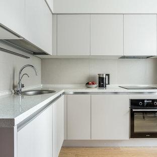 На фото: отдельная, угловая кухня в современном стиле с накладной раковиной, плоскими фасадами, черной техникой, паркетным полом среднего тона, коричневым полом, серыми фасадами и серым фартуком без острова с