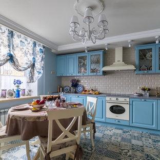 Пример оригинального дизайна интерьера: угловая кухня в стиле шебби-шик с полом из керамической плитки, обеденным столом, монолитной раковиной, фасадами с выступающей филенкой, синими фасадами, фартуком из плитки кабанчик, белой техникой, синим полом и бежевым фартуком без острова
