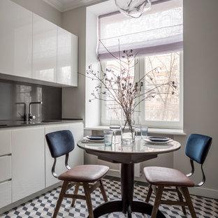 Новый формат декора квартиры: отдельная кухня в современном стиле с врезной раковиной, плоскими фасадами, белыми фасадами, серым фартуком, разноцветным полом и серой столешницей
