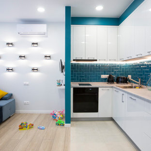 Идея дизайна: угловая кухня в современном стиле с накладной раковиной, плоскими фасадами, белыми фасадами, синим фартуком, фартуком из плитки кабанчик, черной техникой, серым полом и серой столешницей без острова