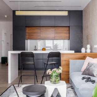 Идея дизайна: прямая кухня-гостиная в современном стиле с плоскими фасадами, черными фасадами, белым фартуком, полуостровом, бежевым полом и белой столешницей