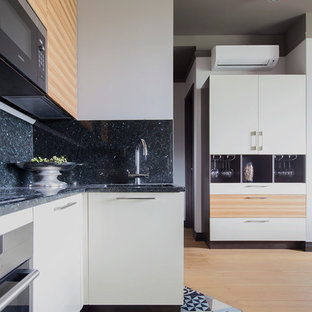 Inspiration for a mid-sized contemporary u-shaped open plan kitchen in Moscow with a single-bowl sink, flat-panel cabinets, beige cabinets, granite benchtops, black splashback, marble splashback, stainless steel appliances, ceramic floors, no island and blue floor.