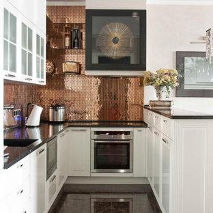 Выдающиеся фото от архитекторов и дизайнеров интерьера: п-образная кухня-гостиная в стиле современная классика с белыми фасадами, фартуком цвета металлик, техникой из нержавеющей стали и полуостровом