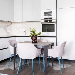 Пример оригинального дизайна интерьера: угловая кухня в современном стиле с обеденным столом, плоскими фасадами, белыми фасадами, белым фартуком, белой техникой, темным паркетным полом и белой столешницей без острова