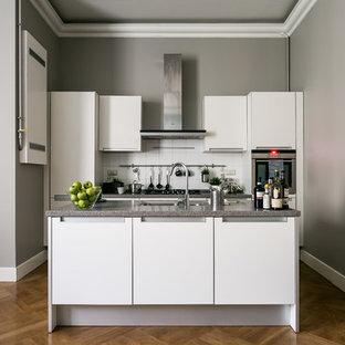Неиссякаемый источник вдохновения для домашнего уюта: параллельная кухня в современном стиле с врезной раковиной, плоскими фасадами, белыми фасадами, белым фартуком, техникой из нержавеющей стали, паркетным полом среднего тона, островом, коричневым полом и серой столешницей