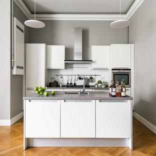 Неиссякаемый источник вдохновения для домашнего уюта: параллельная кухня в современном стиле с плоскими фасадами, белыми фасадами, белым фартуком, техникой из нержавеющей стали, паркетным полом среднего тона, островом, коричневым полом и серой столешницей