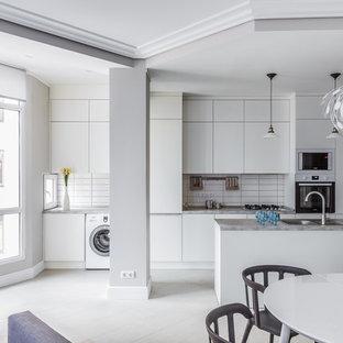 На фото: параллельная кухня-гостиная в современном стиле с накладной раковиной, плоскими фасадами, белыми фасадами, белым фартуком, белой техникой, островом, белым полом и фартуком из плитки кабанчик с