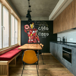 This is an example of an industrial single-wall eat-in kitchen in Moscow with a drop-in sink, flat-panel cabinets, grey cabinets, white splashback, stainless steel appliances, medium hardwood floors, brown floor, black benchtop, no island and recessed.