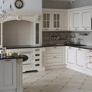 Photo of a mid-sized traditional l-shaped eat-in kitchen in Other with a drop-in sink, raised-panel cabinets, white cabinets, marble benchtops, beige splashback, mosaic tile splashback, white appliances, porcelain floors and with island.