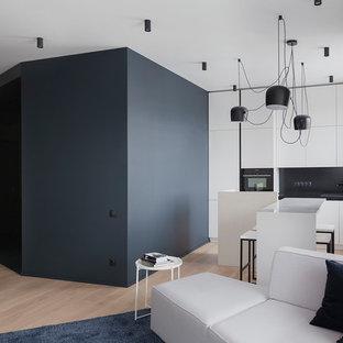 Стильный дизайн: линейная кухня-гостиная в современном стиле с плоскими фасадами, белыми фасадами, черным фартуком, островом, бежевым полом и черной столешницей - последний тренд