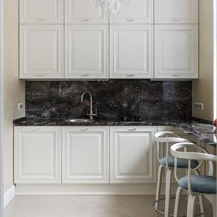 На фото: угловая кухня в классическом стиле с белыми фасадами, одинарной раковиной, фасадами с выступающей филенкой, разноцветным фартуком и фартуком из каменной плиты без острова с