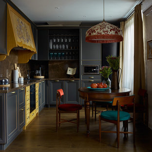 モスクワの中サイズのエクレクティックスタイルのおしゃれなキッチン (落し込みパネル扉のキャビネット、グレーのキャビネット、茶色いキッチンパネル、黒い調理設備、アイランドなし、大理石カウンター、濃色無垢フローリング) の写真