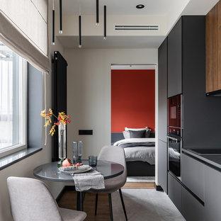 Пример оригинального дизайна: маленькая кухня в современном стиле с плоскими фасадами, серым полом, серой столешницей, обеденным столом, серыми фасадами и черной техникой