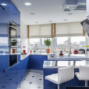 Photo of a large contemporary u-shaped open plan kitchen in Moscow with an integrated sink, flat-panel cabinets, blue cabinets, quartz benchtops, white splashback, panelled appliances, ceramic floors, a peninsula and window splashback.