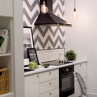 Imagen de cocina comedor lineal, escandinava, de tamaño medio, sin isla, con armarios con paneles lisos, puertas de armario blancas, salpicadero multicolor, suelo de baldosas de porcelana y electrodomésticos negros