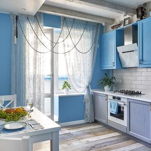 На фото: отдельная кухня в морском стиле с фасадами с утопленной филенкой, синими фасадами, белым фартуком, белой техникой, разноцветным полом и белой столешницей с