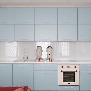 Стильный дизайн: линейная кухня в стиле ретро с накладной раковиной, плоскими фасадами, синими фасадами, белым фартуком, белой техникой и белой столешницей - последний тренд
