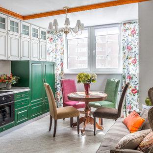 Создайте стильный интерьер: маленькая линейная кухня-гостиная в стиле фьюжн с фасадами с выступающей филенкой, зелеными фасадами, белым фартуком, черной техникой, серым полом и белой столешницей без острова - последний тренд