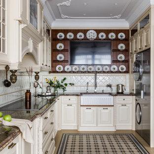 Пример оригинального дизайна: большая параллельная кухня в классическом стиле с обеденным столом, раковиной в стиле кантри, фасадами с выступающей филенкой, бежевыми фасадами, гранитной столешницей, бежевым фартуком, фартуком из керамической плитки, техникой из нержавеющей стали, полом из керамической плитки, бежевым полом и коричневой столешницей