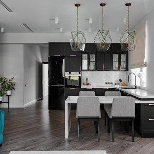 Идея дизайна: п-образная кухня в современном стиле с накладной раковиной, фасадами в стиле шейкер, черными фасадами, серым фартуком, черной техникой, темным паркетным полом, полуостровом, коричневым полом и белой столешницей